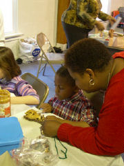 Mother and child making advent decorations in parish hall